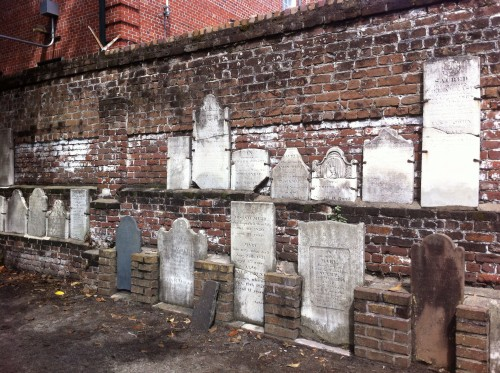 A wall filled with old headstones.
